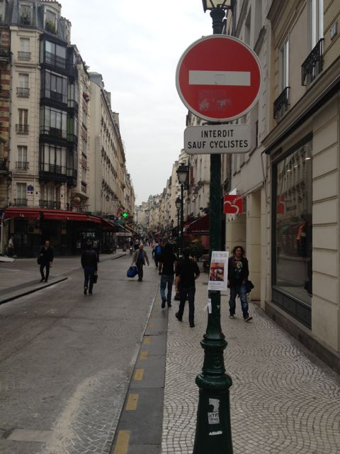 "My Parisian neighborhood, the friendly 2nd Arrondissement, greeted me with its ""Do Not Enter--Except Cyclists"" sign."