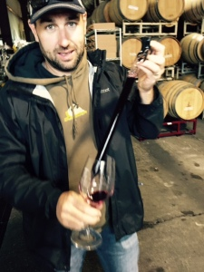 Erik Miller with a wine thief full of Merlot.